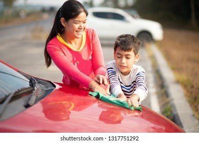 Mother and son cleaning car together