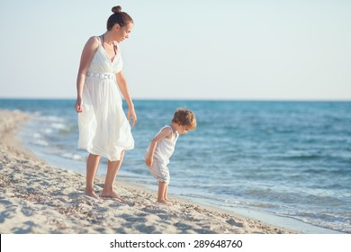Mother and son collecting seashells on the beach