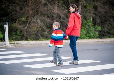Mutter und Sohn, die die Straße überqueren