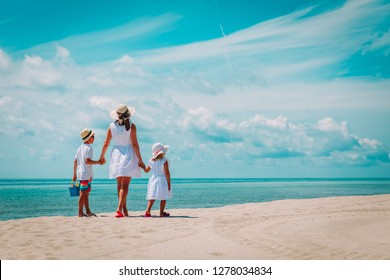 mother with son and daughter walk on beach