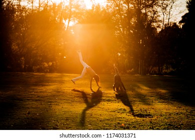 mother and son doing cartwheels in a beautiful city park at sunset