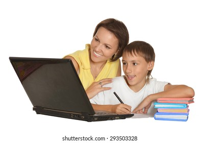 Mother and son doing homework together with laptop