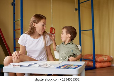 Mother and son draw at a table inside the room.