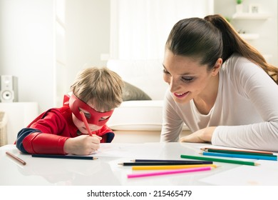 Mother and son drawing and enjoying time together in the living room.