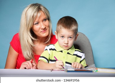 mother and son drawing together, mom helping with homework blue background