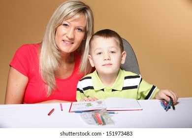 mother and son drawing together, mom helping with homework daycare brown background