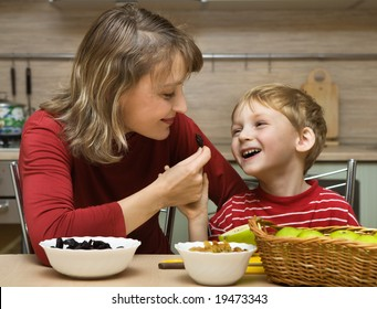 Mother with son is eaten fruit in kitchen