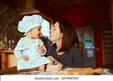 The mother with son eatting cookies  in the kitchen