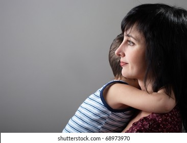 Mother and son embrace on gray gradient background