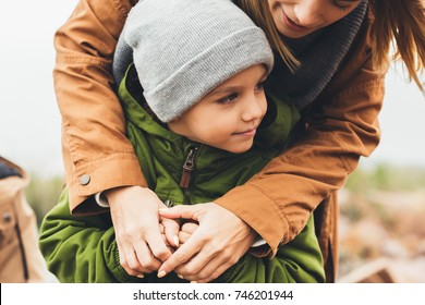 mother and son embracing outdoors on cloudy autumn day