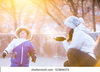 Mother and son enjoying beautiful winter day outdoors, playing with snow at winter time