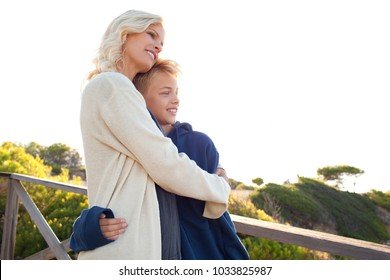 Mother and son enjoying a sunny day out in nature, hugging loving, smiling outdoors. Family coastal leisure activities, well being. Healthy relations, closeness. Travel leisure recreation lifestyle.