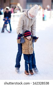 Mother and son enjoying winter ice skating together