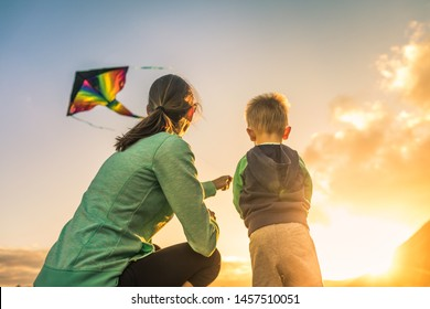 Mother and son flying a kite at sunset.