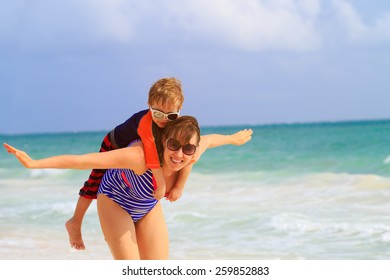 mother and son flying on the beach, family fun