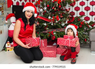 Mother and son in front of Xmas tree holding presents and posing together