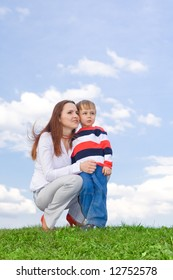 Mother with son at green grass looking up to blue sky