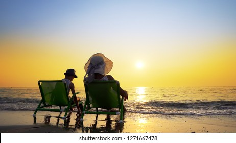 Mother and son with hat sitting on beach chairs looking at the setting sun splashed by sea waves. Travel concept