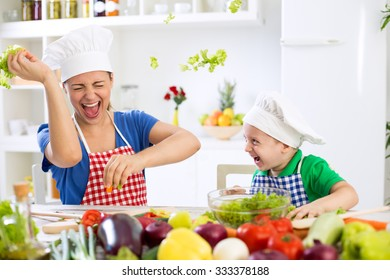 Mother and son have fun in kitchen food war at home