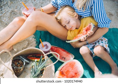 Mother with son have picnic on the beach