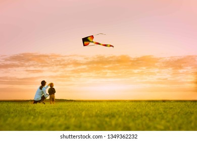 Mother and son having fun flying a kite at sunset.