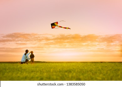 Mother and son having fun flying a kite at sunset, outdoor summer family lifestyle,