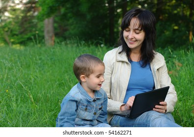 Mother and son having fun with laptop outdoors on the summer green meadow