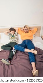Mother with son having fun, mom and her teenager son lying on bed, mother with child relaxing, modern mom with kid at home, top view
