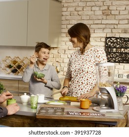 Mother and son having fun in the morning in the kitchen.