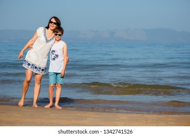 Mother and son having fun on the beach during summer holiday vacation
