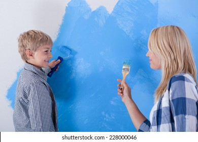 Mother and son having fun from painting the wall, horizontal