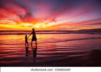 mother and son having fun at sunset on the beach
