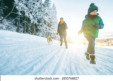Mother and son having a fun. They running with their beagle dog in snowy forest during dog walk. Mother and son relatives and femily values concept image. - Shutterstock ID 1850768827