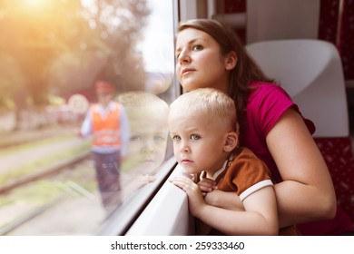 Mother with son in her lap traveling in train.
