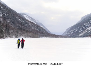 A mother and son hiking on a frozen river surrounded by mountains on a cloudy winter day