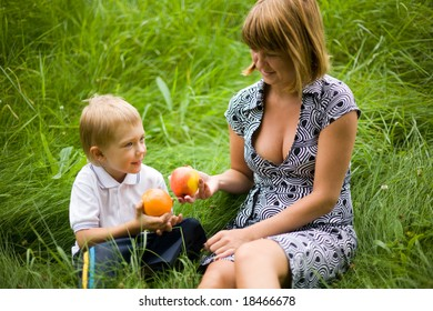 Mother and the son hold an apple and an orange in hands. Game. Summer.