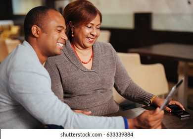 A mother and son hold a computer tablet, talking with a friends