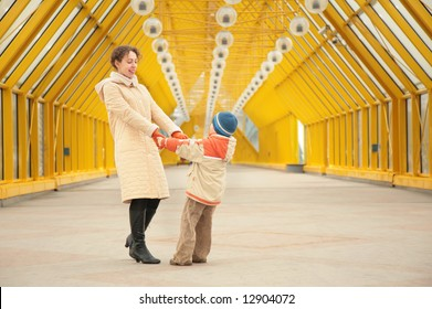 mother and son hold each other for hands on footbridge
