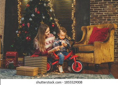Mother and son hold garland and smile in cozy room. Christmas and new year decoration around. Christmas tree and gift boxes on background.