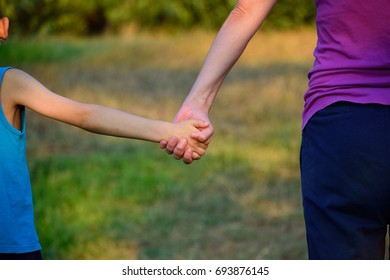 Mother and son hold hands