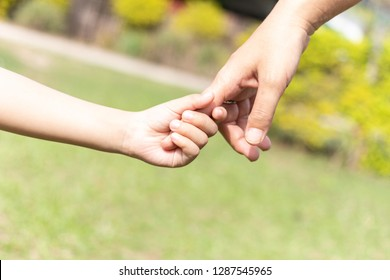 Mother and son holding hand.