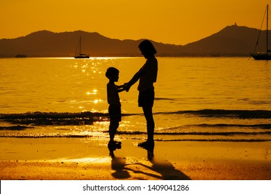 A mother and son A mother and son Holding hand playing on the beach and sea outdoors at sunset in happy holiday vacation time with copy space