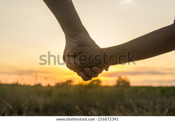Mother and son holding hands into the sunset of a summer day