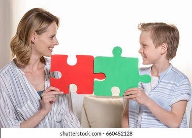 Mother with son holding puzzle pieces