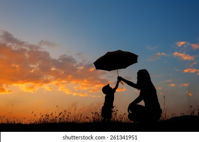 A mother and son holding umbrella and playing outdoors at sunset silhouette