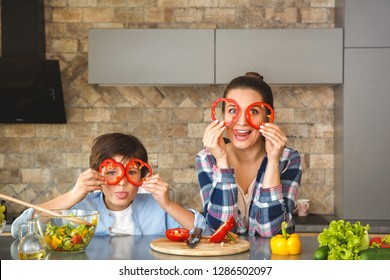 Mother and son at home standing in kitchen leaning on table together covering face with bell pepper circles looking camera grimace playful