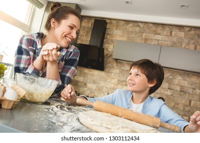 Mother and son at home standing at table in kitchen together looking at each other smiling cheerful while boy rolling dough with pin