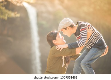 Mother and son hug each other happy together in the forest