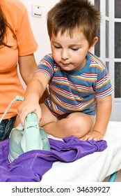 Mother and son ironing