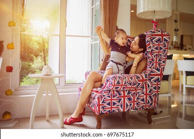 Mother and son are joking on the same sofa chair near a window and sun-filled.